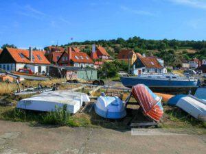 Fischerboote liegen an Land, idyllische Häuser im Hintergrund, Bornholm