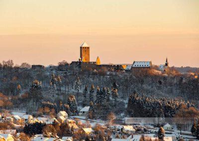 Winter an der Burg Lichtenberg in der Westpfalz. Im Vordergrund sieht man Thalichtenberg (Kreis Kusel). Die Landschaft ist mit Schnee bedeckt