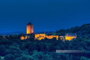 Blaue Stunde an der beleuchteten Burg Lichtenberg. Dunkle Bäume und dunkler Nachthimmel umgeben die Burg