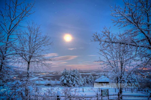 Nachtpanorama des Potzbergs im Winter. Heller Mond leuchtet über der schneebedeuten Landschaft. Aufgenommen im Landkreis Kusel (Westpfalz)