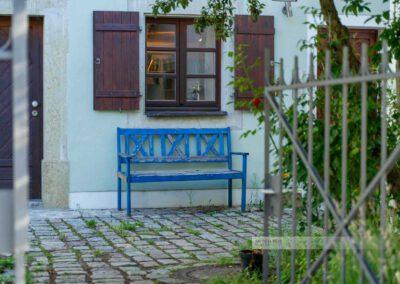 Idyllische Bank in einem Garten einer Gasse im Stadtteils StadtamHof im Welterbe Regensburg