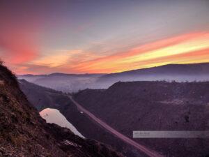Sonnenaufgang am Steinbruch in Theisbergstegen am Remigiusberg. Im Tal liegt ein See. (Kreis Kusel, Westpfalz, Pfälzer Bergland)